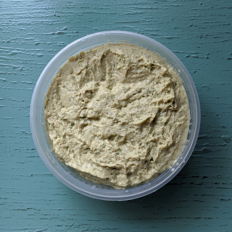 Creamy textured and lightly green colored Cilantro Jalapeño Hummus is pictured in a circular container and topped with fresh sliced Jalapeño on a wood table background.