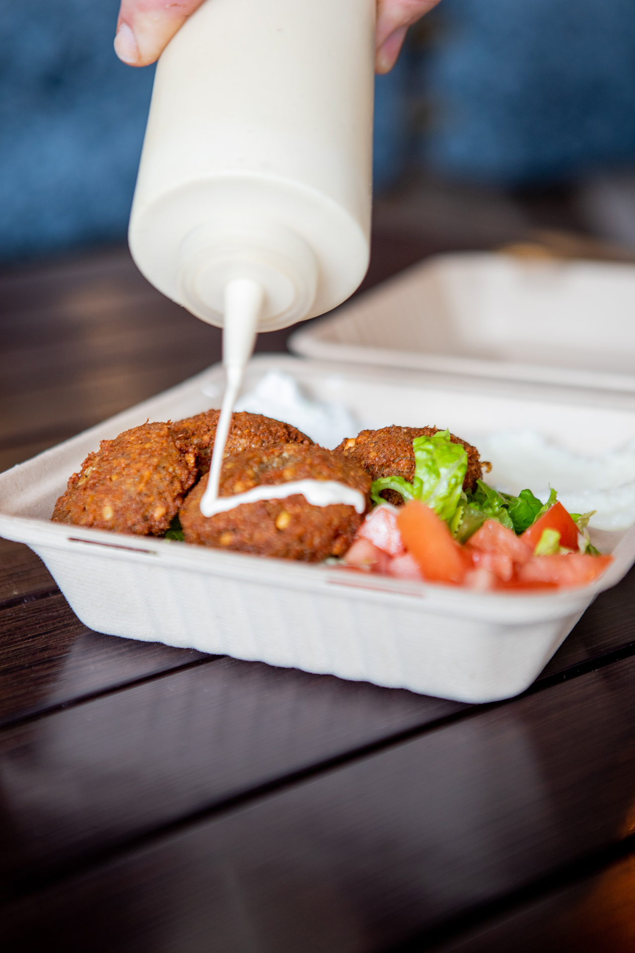 Inside the Hummus Labs restaurant, on top of a black metalic table a Falafel plate is being topped with Tahini sauce. The plate is accompanied with a salad, spicy labneh and tzatziki sides.