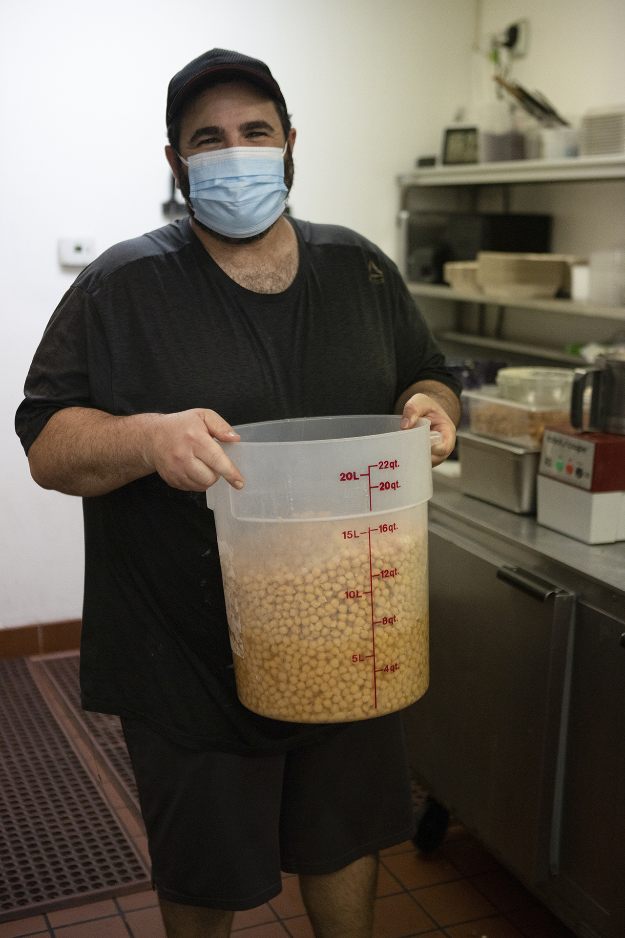 In the Hummus Labs kitchen, chef Joseph Badaro is pictured wearing a black shirt, black hat and a light blue mask. Chef is holding a large container filled with chickpeas.