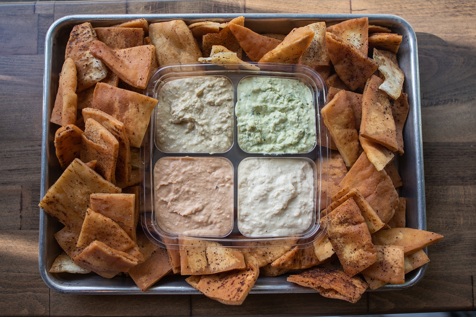The Party Pack is pictured in a square container with four side orders of our signature Hummus flavors, Classic Hummus, Cilantro Jalapeño Hummus, Roasted Tomato Habanero Hummus, and Cumin Lime Hummus. The Party Pack container is centered on a large rectangular metallic tray and is surrounded by fresh pita chips. The tray is on a wood table background.