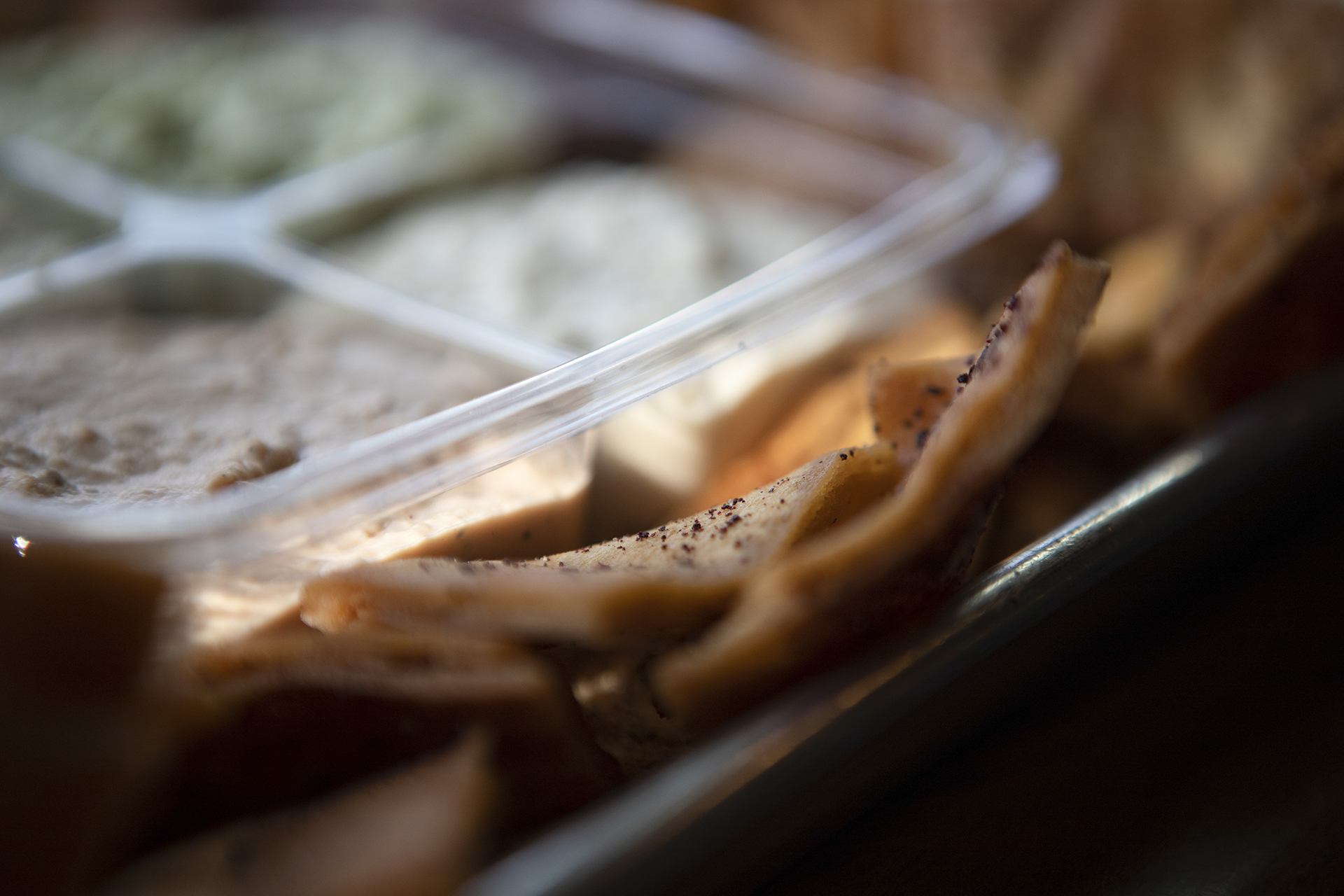 On a metallic tray Pita chips are pictured up close with a party pack filled to the brim with various hummus flavors blurred in the background.