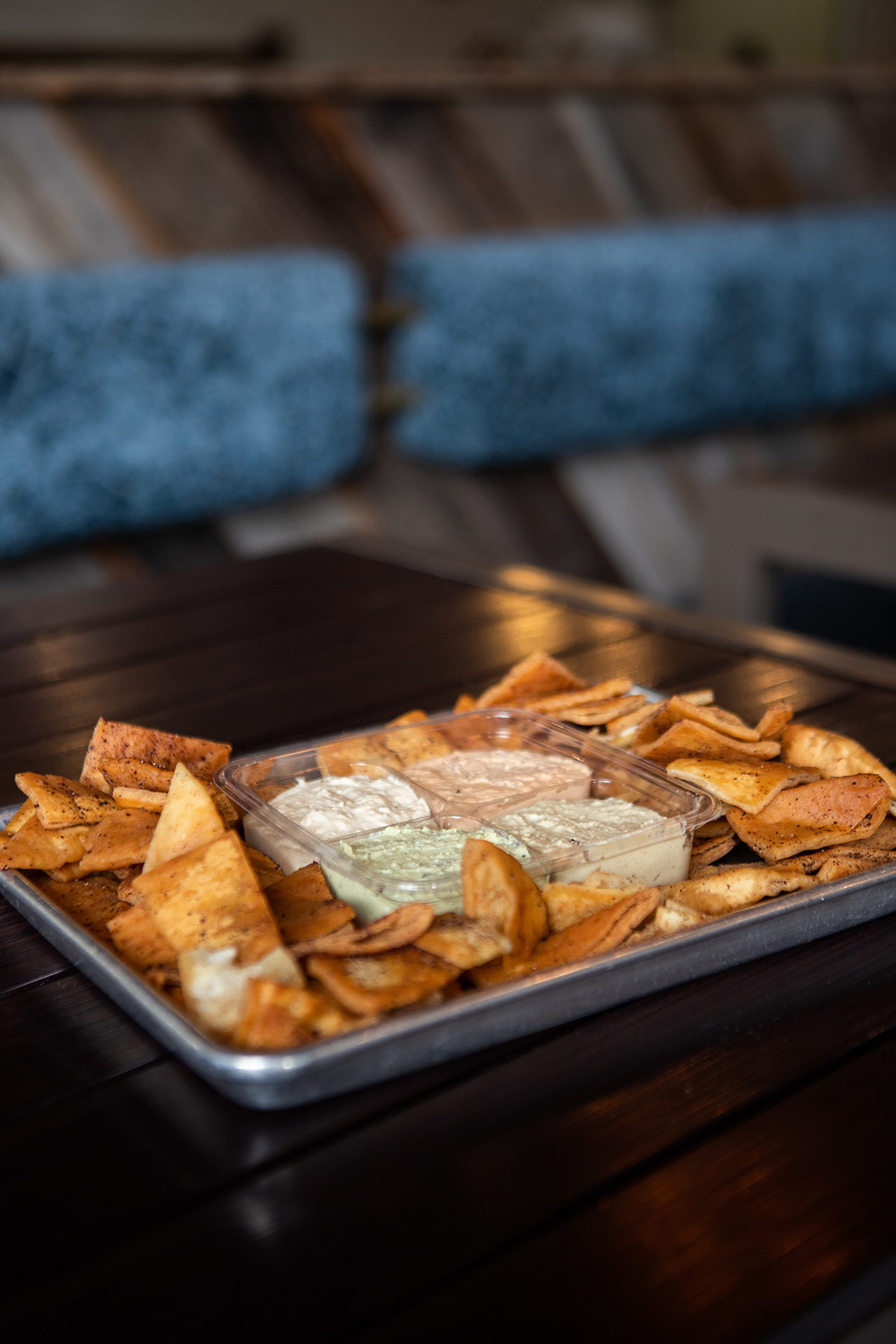 The Party Pack is pictured in a square container with four side orders of our signature Hummus flavors, Classic Hummus, Cilantro Jalapeño Hummus, Roasted Tomato Habanero Hummus, and Cumin Lime Hummus. The Party Pack container is centered on a large rectangular metallic tray and is surrounded by fresh fried pita chips. The tray is placed on a black metallic table.