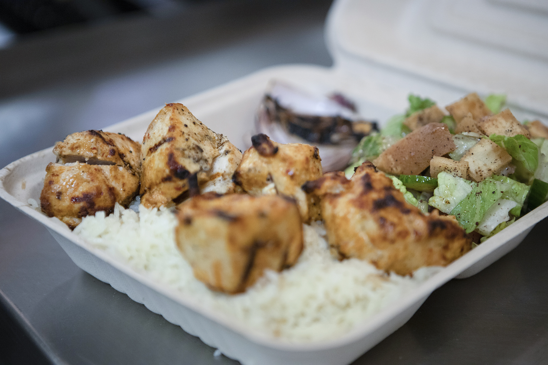 The Chicken Kabab platter is pictured on a smooth metallic table top. The kabab is served over a bed or rice and accompanied by sides of fresh grilled vegetables and a fattoush salad.