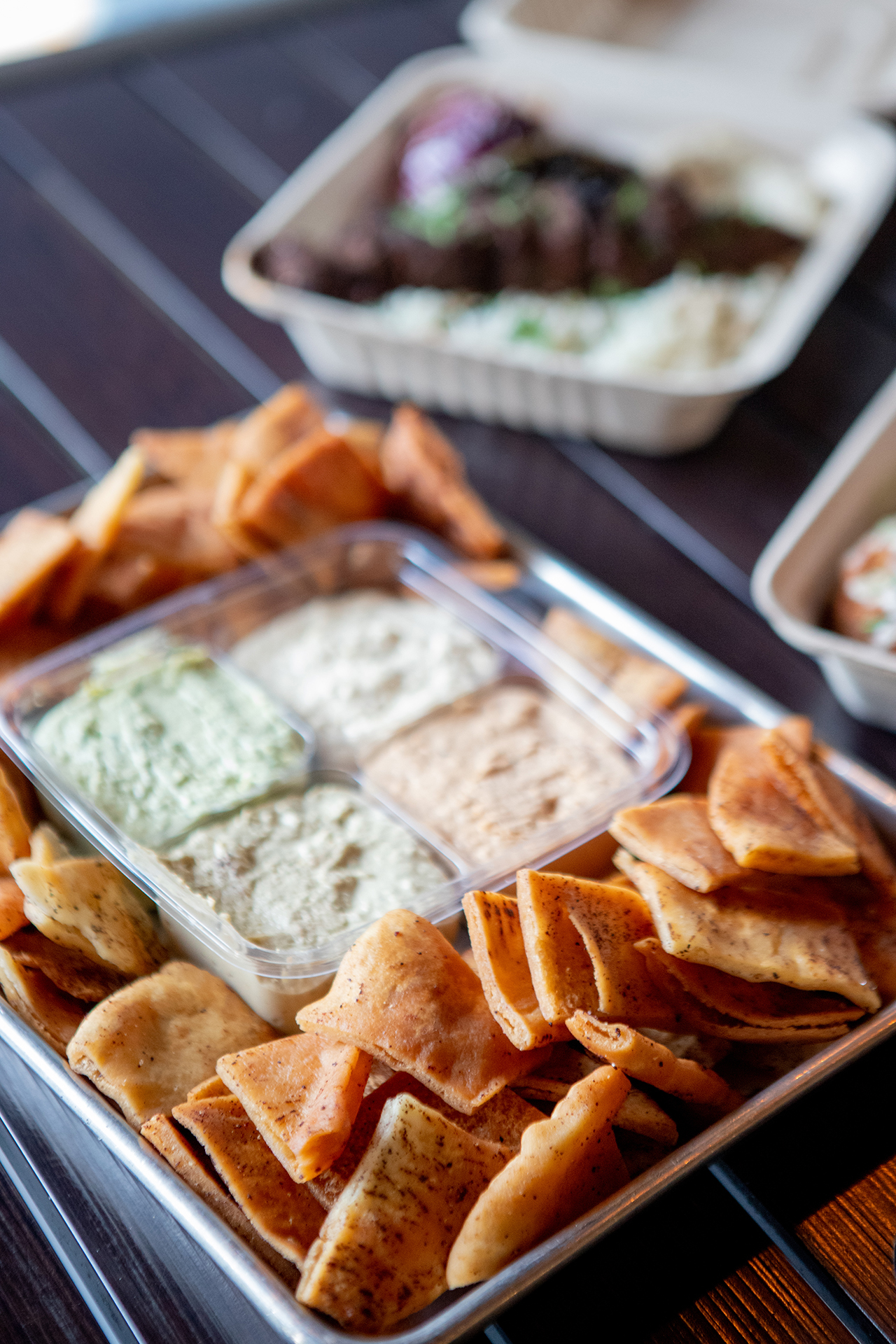 The Party Pack is pictured in a square container with four side orders of our signature Hummus flavors, Classic Hummus, Cilantro Jalapeño Hummus, Roasted Tomato Habanero Hummus, and Cumin Lime Hummus. The Party Pack container is centered on a large rectangular metallic tray and is surrounded by fresh fried pita chips. The tray is placed on a black metallic table and accompanied by a Chicken Kebab platter and a Beef Kafta Kabab platter that are blurred in the background.