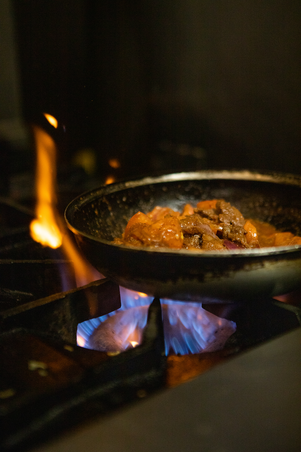 In the hummus labs kitchen beef shawarma is pictured up close in a saute pan while cooked over the stove top. The flame underneath is blue and purple in color and there are red flames coming up around the back of the sauté pan.