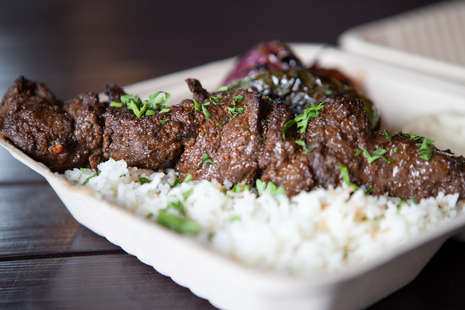 A Filet Mignon platter is pictured on a black metalic table. The Fillet Mignon platter is served on a bed or rice, with Garlic Paste, and grilled vegetable sides. The plate is topped with parsley garnish.