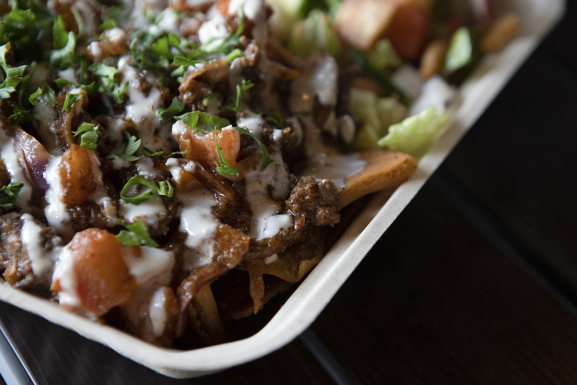 Beef Shawarma Nachos are pictured up close on top of a black metallic table in the hummus labs restaurant. The plate is topped with tahini sauce and accompanied by a side of salad and tzatziki.