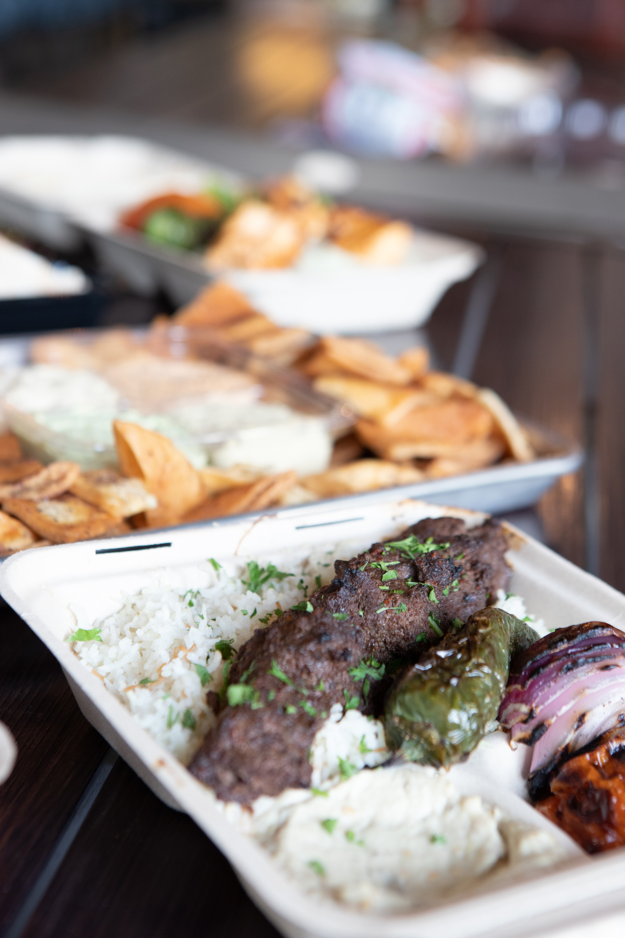 A Beef Kafta Kabob platter is pictured in the foreground on a black metalic table. The Kafta plate is served on a bed or rice, with classic hummus, and grilled vegetable sides. In the blurred background the Kafta Plate is accompanied by a Chicken Kabob platter and a Party Pack that is surrounded by Pita chips.