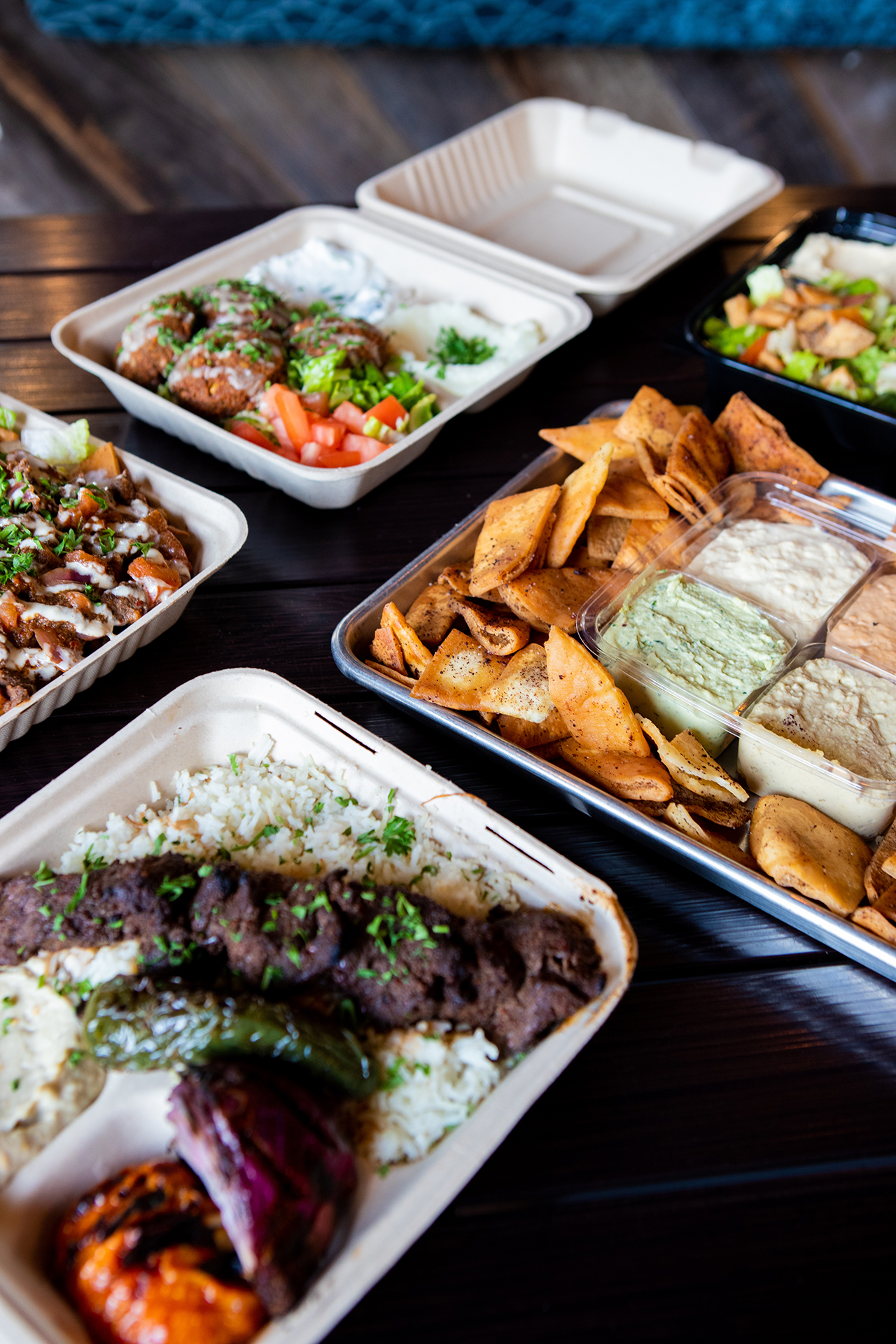 Inside the Hummus Labs restaurant, on top of a black metalic table, four signature dishes are pictured. The dishes are laid out on a 45 degree angle and staggered. Beef Shawarma Nachos. A Filet Mignon platter served with rice, grilled vegetables, and classic hummus. A Falafel platter served with Spicy Labneh, Garlic Paste, and Salad. A Party Pack with Classic Hummus, Cilantro Jalapeño Hummus, Roasted Tomato Habanero Hummus, Cumin Lime Hummus, and surrounded by fresh fried pita chips.