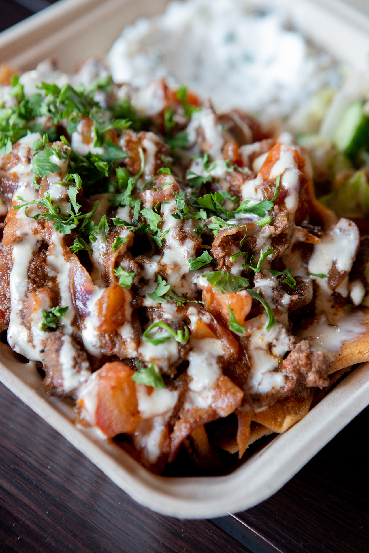 Chicken Shawarma Nachos are pictured up close on top of a black metallic table in the hummus labs restaurant. The plate is topped with tahini sauce and accompanied by a side of salad and tzatziki.