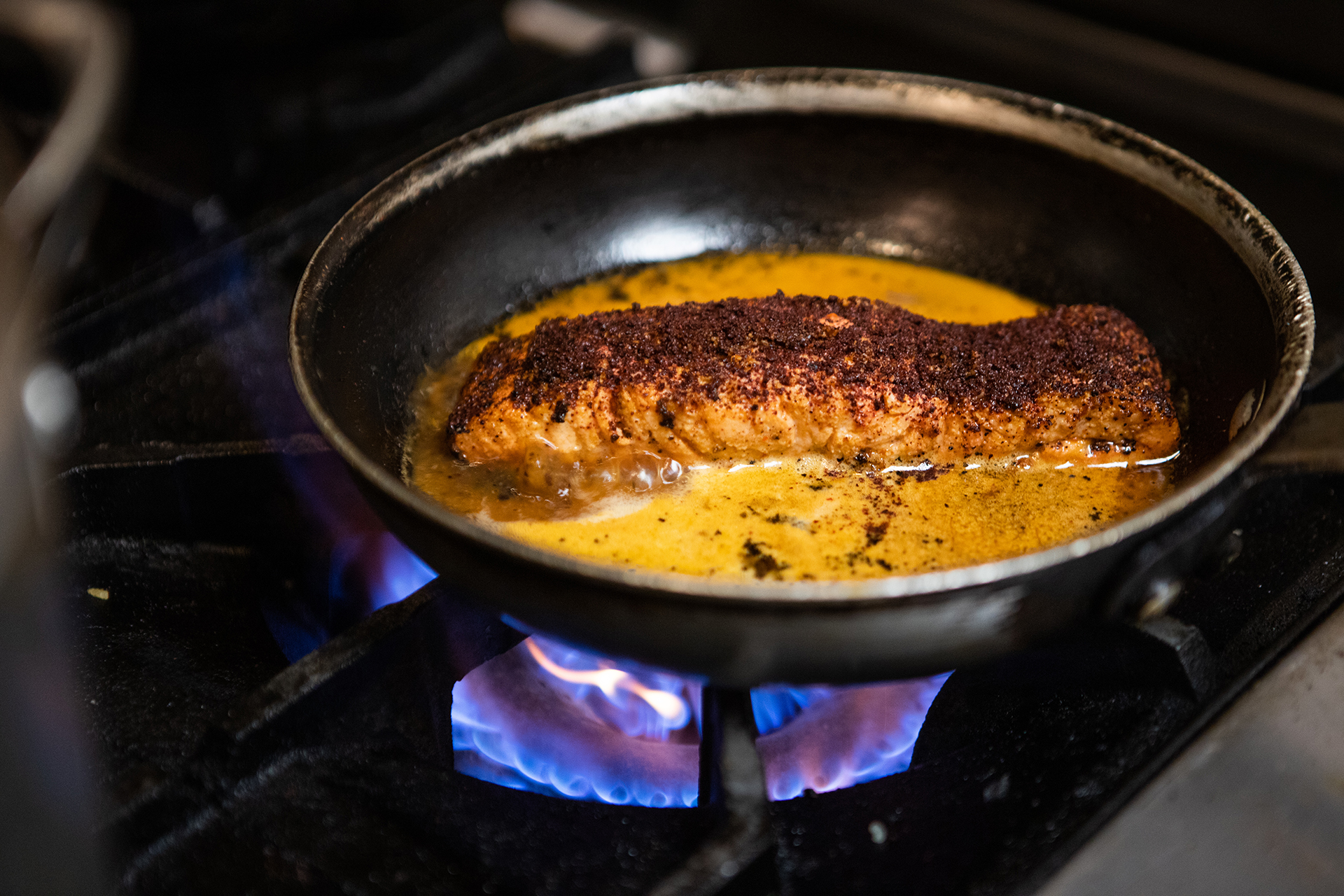 The Mediterranean Salmon is pictured cooking over fire in a sauté pan with a brightly colored orange sauce. A vibrant blue and purple stove top flame can be seen underneath the sauté pan.