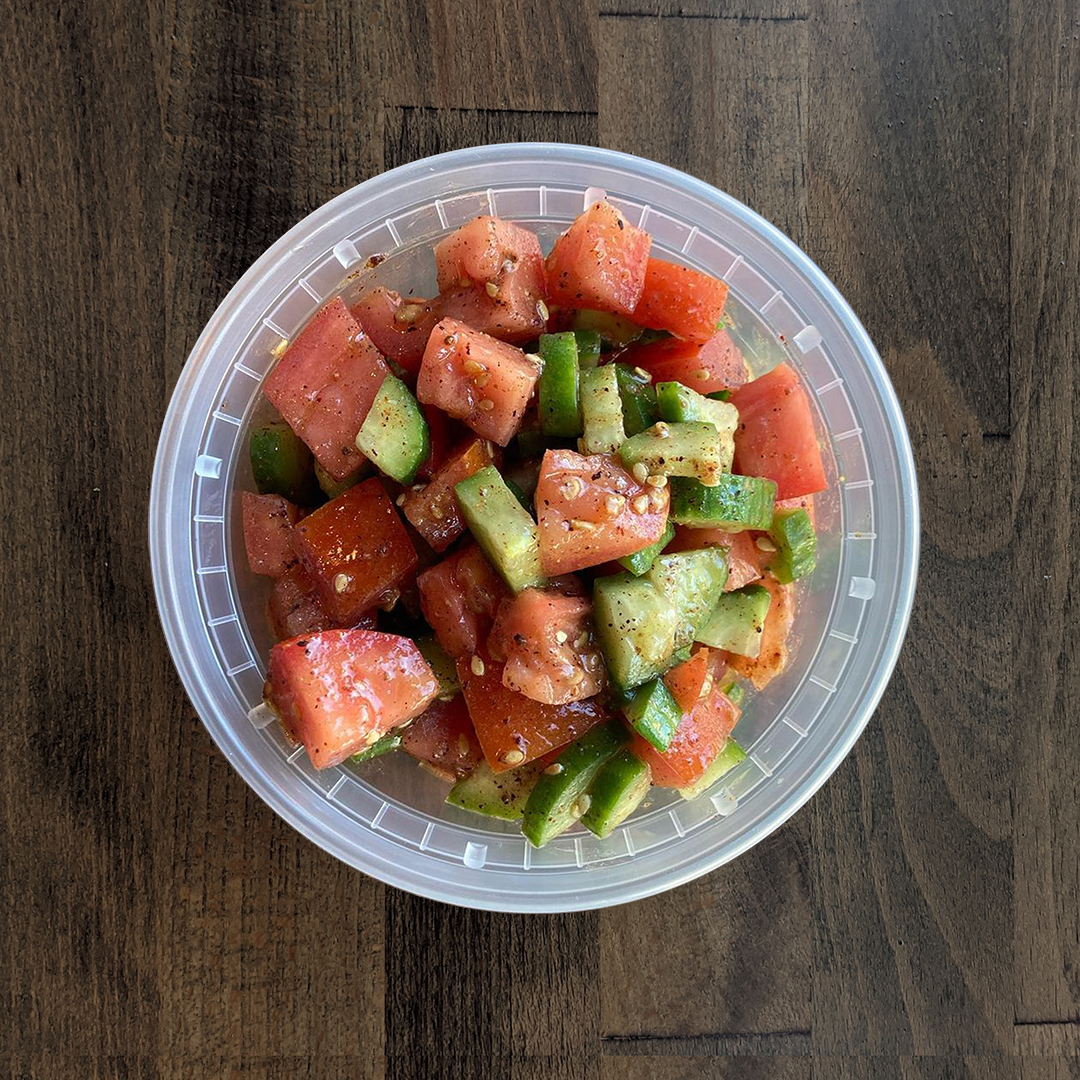 Brightly colored Cucumber Tomato Salad is pictured in a circular container on a wood table background.