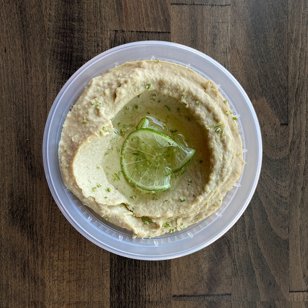 Silky smooth and lightly green colored Cumin Lime Hummus is pictured in a circular container and topped with freshly sliced Lime on a wood table background.