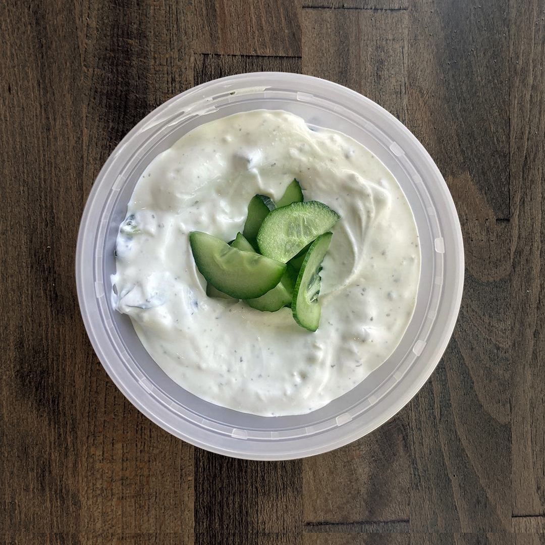 Silky Smooth tzatziki is pictured in a circular container on a wood table background. The tzatziki is topped with freshly cut cucumber chips.