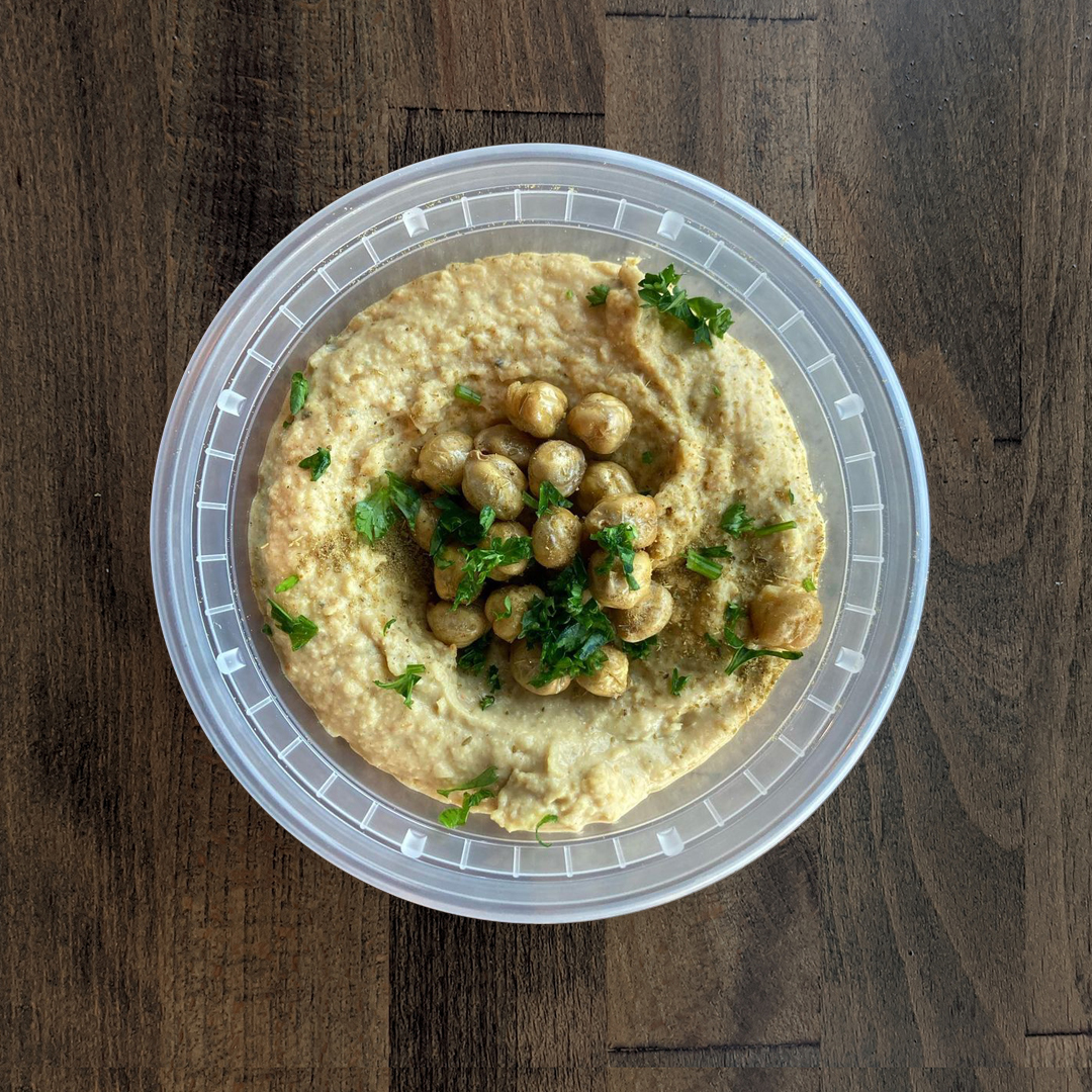 Silky smooth Curry Hummus is pictured in a circular container topped with Chickpeas and Parsley on a wood table background.