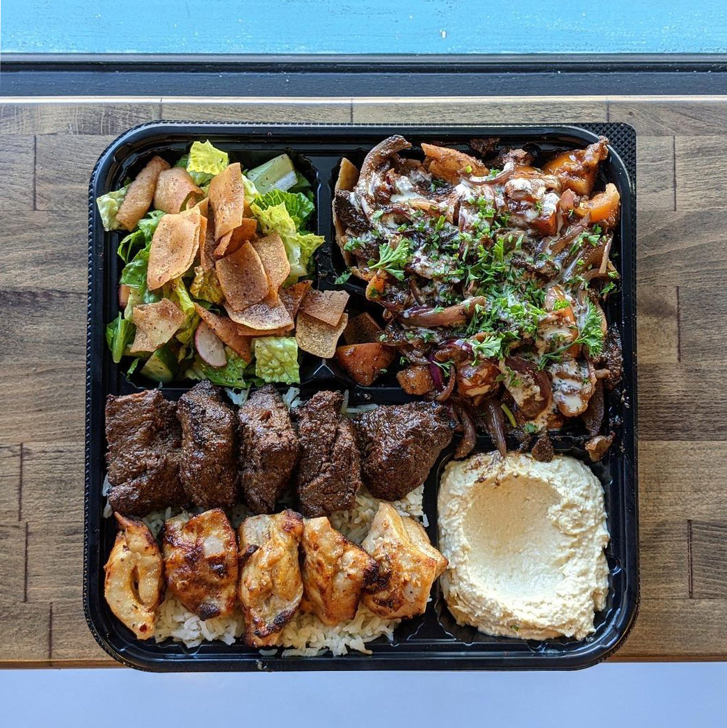The Ultimate Platter is pictured in a large black tray. Chicken kabob and filet mignon skewers served on a bed of rice, served with Mini Beef Shawarma Nachos, a fattoush salad and classic hummus on a wood table.